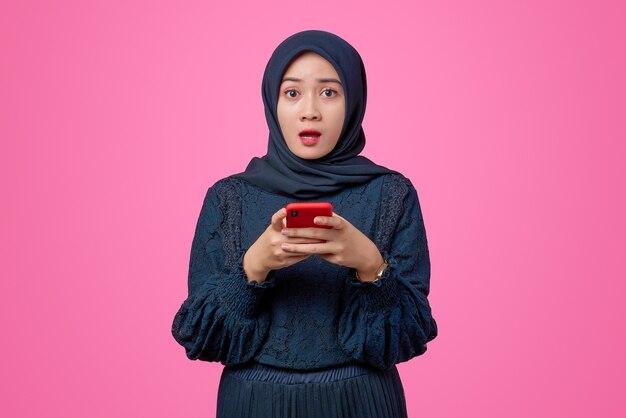 Portret van mooie aziatische vrouw met smartphone met geschokte uitdrukking