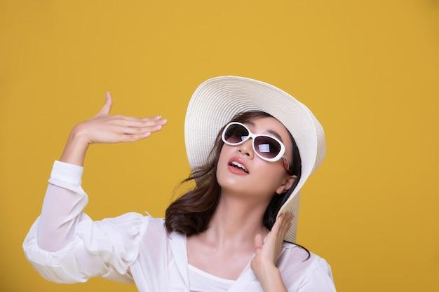 Portret van mooie aziatische vrouw met zonnebril en hoed