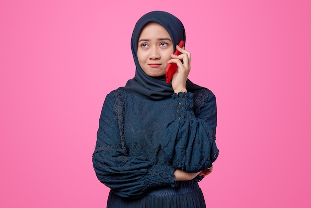 Portret van mooie aziatische vrouw praten door smartphone met verveelde uitdrukking