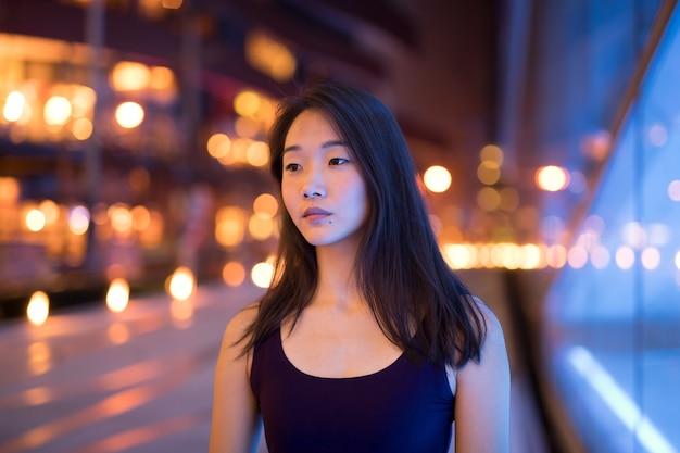 Portret van mooie aziatische vrouw 's nachts buiten te denken