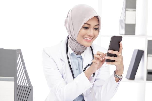Portret van mooie aziatische vrouwelijke arts die mobiele telefoon met behulp van