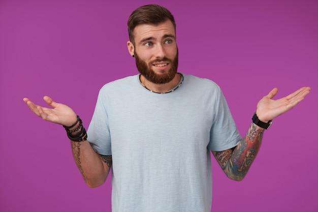 Portret van mooie bebaarde brunette met tattoos die opzij kijken en zijn voorhoofd rimpelen, poseren op paars en verward de handpalmen opheffen