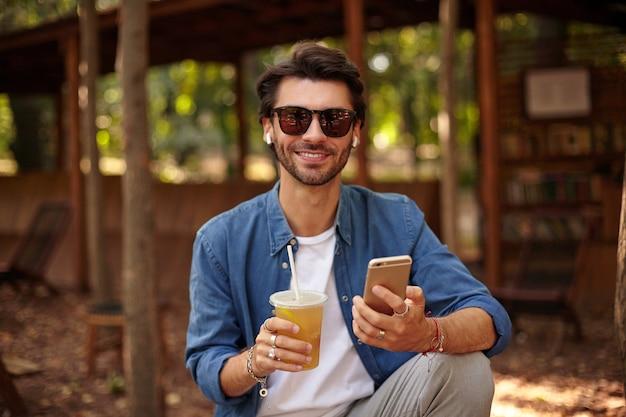 Portret van mooie bebaarde man in zonnebril poseren over openbare buitenruimte, kijken met charmante glimlach, mobiele telefoon en kopje sap in zijn handen houden