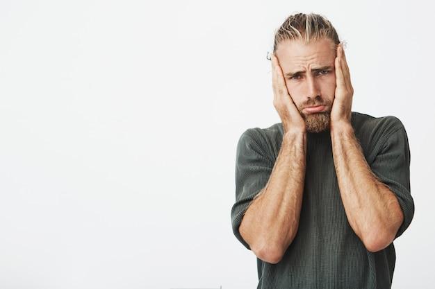 Portret van mooie bebaarde man met hoofd in handen met ongelukkige uitdrukking