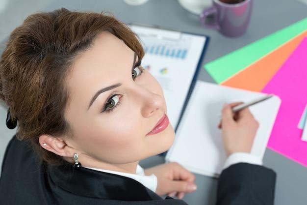 Portret van mooie bedrijfsvrouw die op werk terugkijkt. bovenaanzicht.