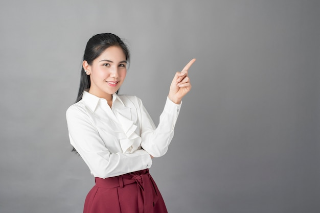 Portret van mooie bedrijfsvrouw op grijze achtergrond, studioschot