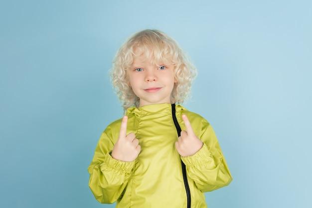 Portret van mooie blanke kleine jongen geïsoleerd op blauwe muur