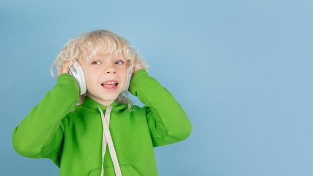 Portret van mooie blanke kleine jongen geïsoleerd op blauwe studio wall