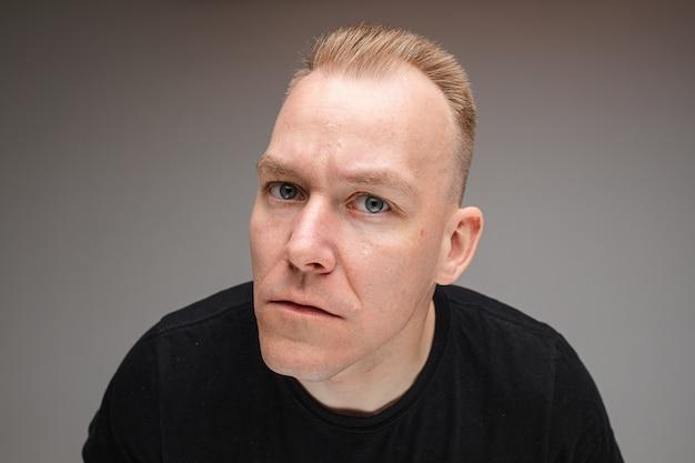 Portret van mooie blanke man in zwart t-shirt en probeert iets te zien, foto geïsoleerd op een grijze muur