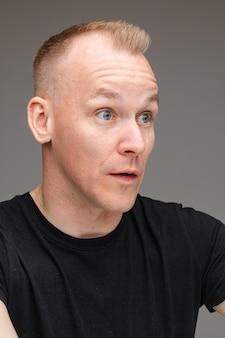 Portret van mooie blanke man in zwart t-shirt kijkt naar iets interessants met grote ogen en open mond geïsoleerd op een grijze achtergrond gray