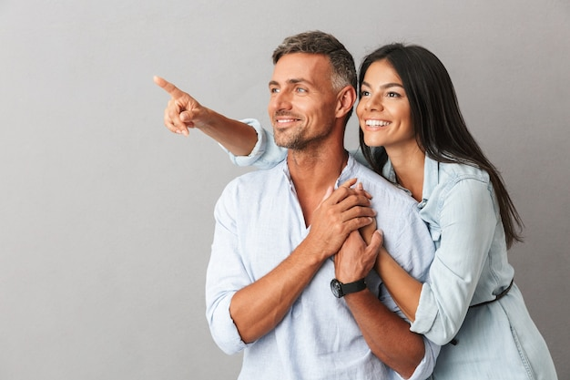 Portret van mooie blanke mensen man en vrouw in basiskleding samen knuffelen en opzij kijken, geïsoleerd over grijs