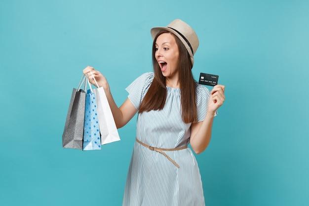Portret van mooie blanke vrouw in zomerjurk, strohoed met pakketten met aankopen na het winkelen, bankcreditcard geïsoleerd op blauwe pastelachtergrond. kopieer ruimte voor advertentie.