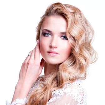Portret van mooie blanke vrouw met blond krullend haar poseren.