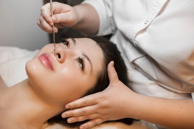 Portret van mooie blanke vrouw met donker haar, leunend op een spa-bed met gezichtsreiniging door een schoonheidsspecialist in wellness-spa salon.