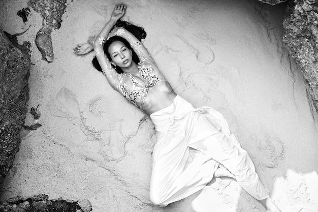 Portret van mooie blanke vrouw model met donker lang haar in klassieke wijde pijpen broek liggend op wit zand op het strand in de buurt van rotsen. bovenaanzicht