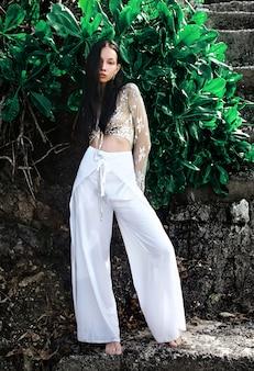 Portret van mooie blanke vrouw model met donker lang haar in wijde pijpen klassieke broek poseren in de buurt van groene tropische exotische bladeren achtergrond