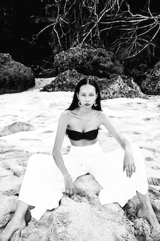 Portret van mooie blanke vrouw model met donker lang haar in wijde pijpen klassieke broek zittend op zomer strand met wit zand in de buurt van rotsen