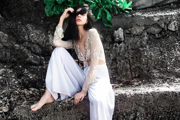 Portret van mooie blanke vrouw model met lang donker haar in wijde pijpen klassieke broek poseren in de buurt van rotsen en groene tropische exotische bladeren achtergrond