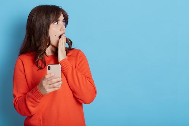 Portret van mooie blanke vrouw schokkend met iets op mobiele telefoon