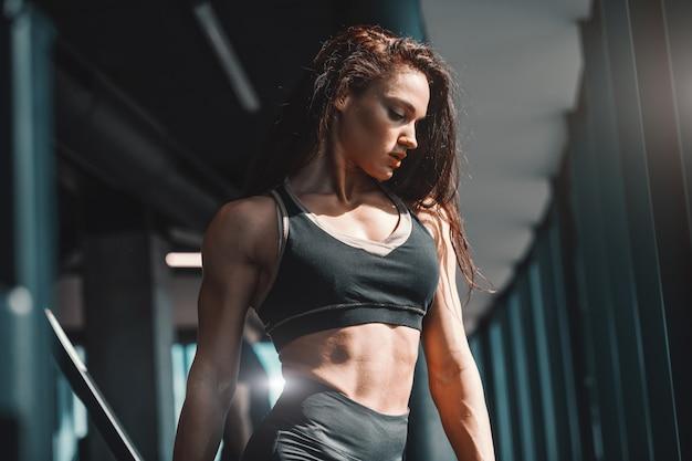 Portret van mooie blanke vrouwelijke bodybuilder poseren in de sportschool. maak spieren, geen excuses.