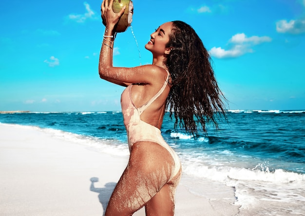 Portret van mooie blanke zonnebaden vrouw model met donker lang haar in beige zwembroek poseren op zomer strand met wit zand op blauwe lucht en de oceaan