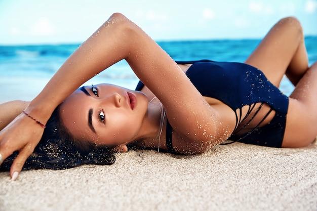 Portret van mooie blanke zonnebaden vrouw model met donker lang haar in zwarte zwembroek liggend op zomer strand met wit zand op blauwe lucht en de oceaan