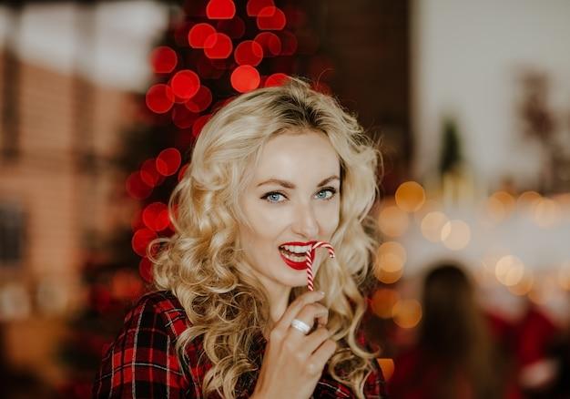 Portret van mooie blauwe ogen vrouw met blond haar en rode lippen poseren met kerst kaars