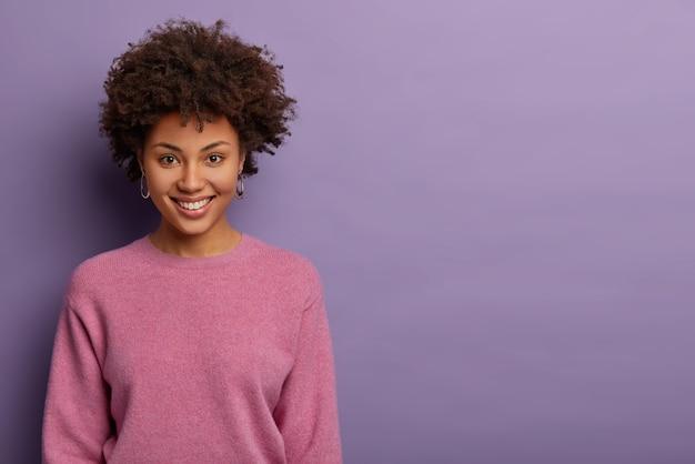 Portret van mooie blije vrouw heeft afro-haar, glimlacht vreugdevol, krijgt aangenaam nieuws