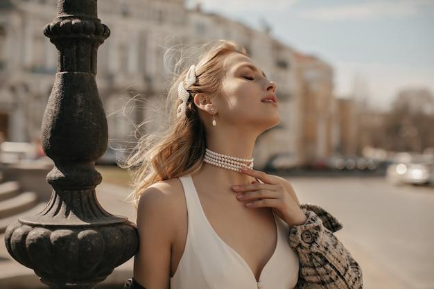 Portret van mooie blonde dame in stijlvolle witte zijden jurk, geruit jasje en parelketting die zachtjes de nek aanraakt en poseert op het stadsplein
