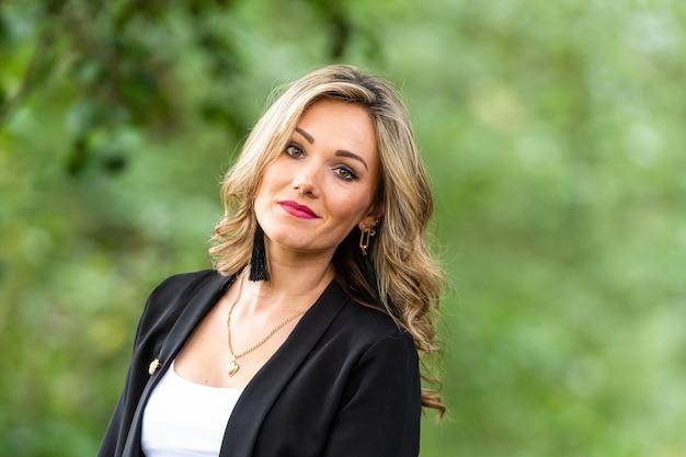 Portret van mooie blonde glimlachende vrouw in bos