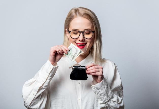 Portret van mooie blonde in wit overhemd met geld en portemonnee op witte muur
