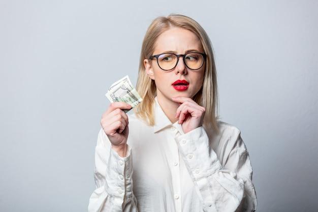 Portret van mooie blonde in wit overhemd met geld op witte muur