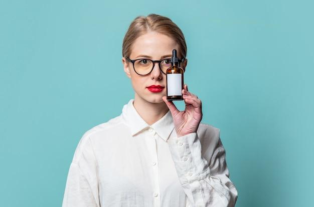 Portret van mooie blonde in wit overhemd met kosmetische fles op blauwe muur