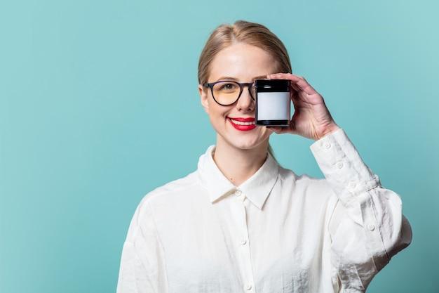 Portret van mooie blonde in wit overhemd met roomkruik op blauwe muur