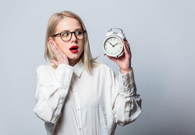 Portret van mooie blonde in wit overhemd met wekker op witte muur
