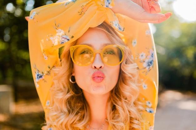 Portret van mooie blonde modieuze vrouw in gele blouse die zonnebril draagt