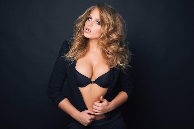 Portret van mooie blonde sexy vrouw op zwarte achtergrond