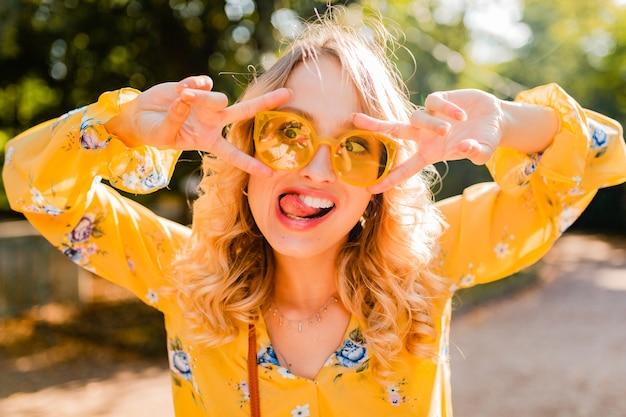 Portret van mooie blonde stijlvolle emotionele vrouw in gele blouse dragen van een zonnebril, grappige gekke gezichtsuitdrukking