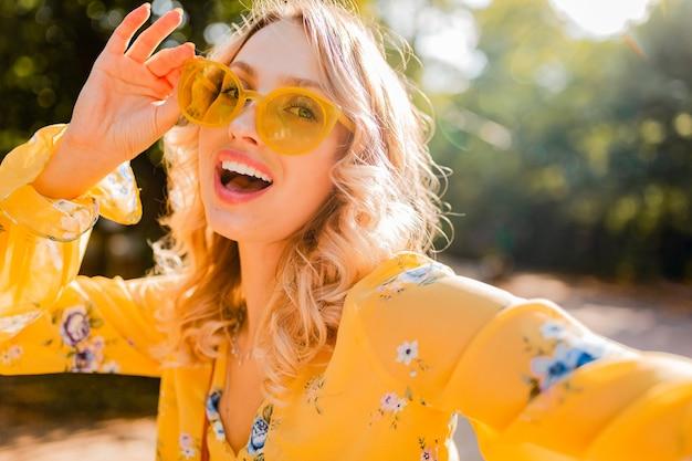 Portret van mooie blonde stijlvolle lachende vrouw in gele blouse dragen van een zonnebril selfie foto maken