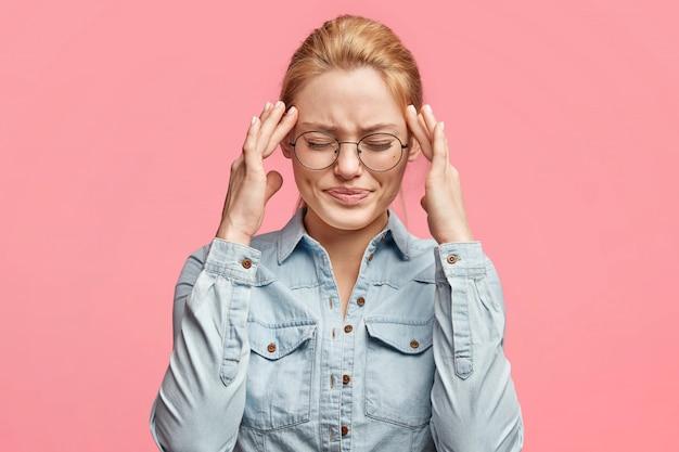 Portret van mooie blonde studente wordt overwerkt, houdt de handen op de slapen, voelt zich moe na een slapeloze nacht, draagt een bril en een spijkerjasje, heeft vreselijke hoofdpijn. vermoeidheid leuke vrouw