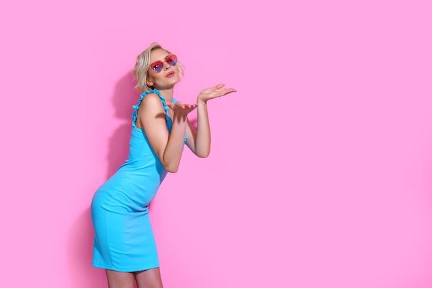 Portret van mooie blonde vrouw in blauwe jurk met zonnebril poseren op roze studio achtergrond