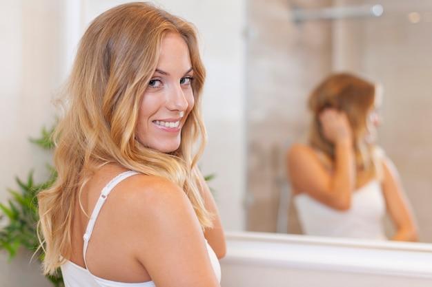 Portret van mooie blonde vrouw in de badkamer