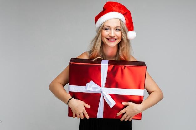Portret van mooie blonde vrouw in rode kerstmuts omarmen verpakt kerstcadeau in rood inpakpapier en witte strik. blond meisje glimlachend in de camera met cadeau in handen.
