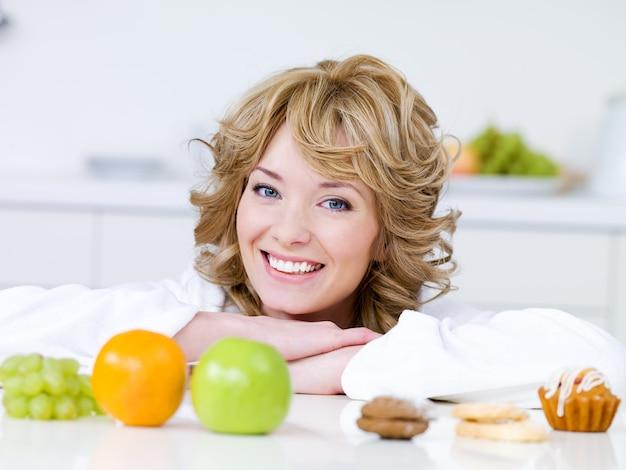 Portret van mooie blonde vrouw met fruit en gebak, zittend op de keuken