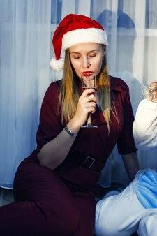 Portret van mooie blonde vrouw met glas champagne in nieuwjaarshoed