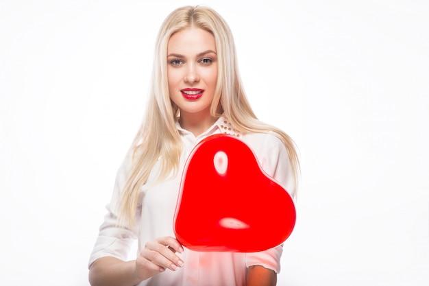 Portret van mooie blonde vrouw met heldere make-up en rood in hand hart
