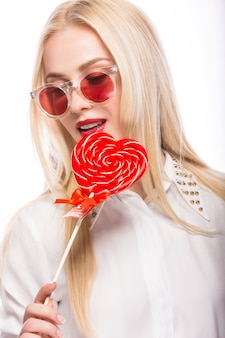 Portret van mooie blonde vrouw met heldere make-up en rood in hand suikergoedhart