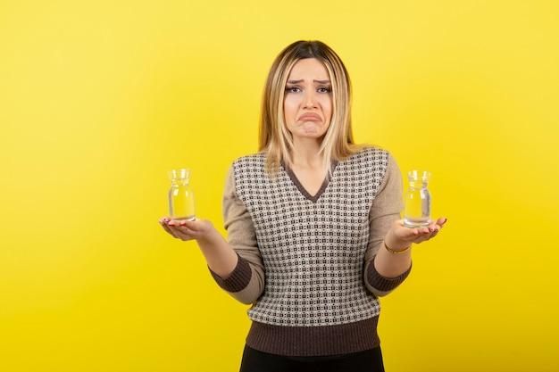 Portret van mooie blonde vrouw met twee glazen stilstaand water.