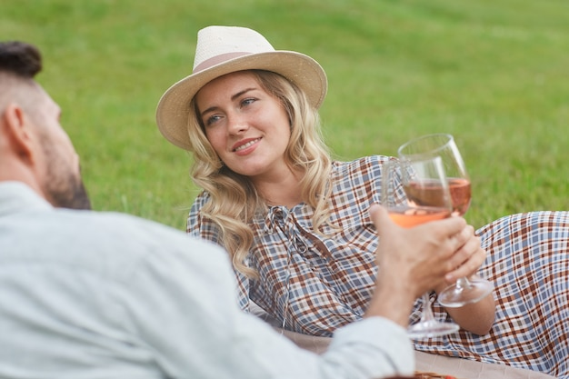 Portret van mooie blonde vrouw met wijnglas terwijl u geniet van picknick op groen gras tijdens romantische date buitenshuis