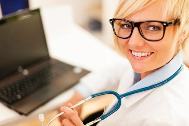 Portret van mooie blonde vrouwelijke arts die glazen draagt